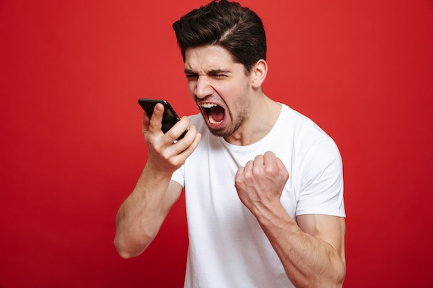 Portrait of a furious young man in white t-shirt