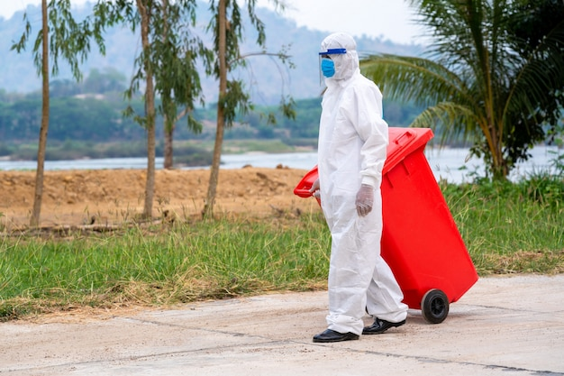 Portrait of garbage collector in hazmat ppe protective clothing wear medical rubber with truck loading waste and trash bin,coronavirus disease 2019,coronavirus has turned into a global emergency.