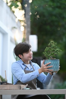 Portrait of gardener man smiling and holding bonsai tree pot while sitting at his home garden.