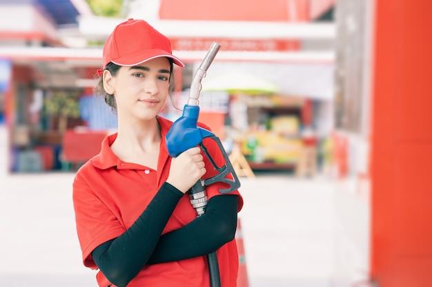 Портрет женщины работника азс счастливые улыбающиеся с топливной форсункой для работы по заправке автомобильного бензина.