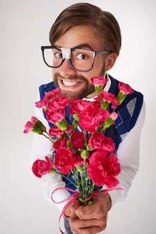 Portrait of geek holding flower bouquet isolated