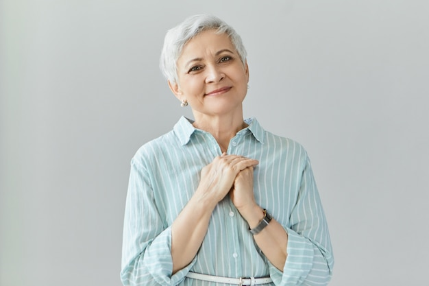 Portrait of generous kind mature senior female in stylish shirt holding hands clasped on her chest, feeling grateful for great present on her birthday. elderly woman expressing appreciation