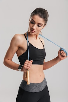 Portrait of gentle muscular woman looking aside and holding skipping rope on her neck, isolated over gray wall