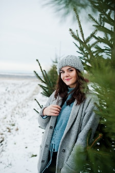 Portrait of gentle woman in gray coat and hat against christmas tree outdoor.