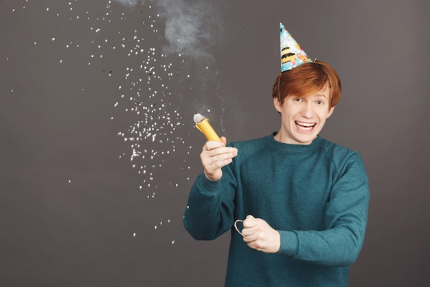 Portrait of ginger boy on spending birthday with friends in warm and happy atmosphere.
