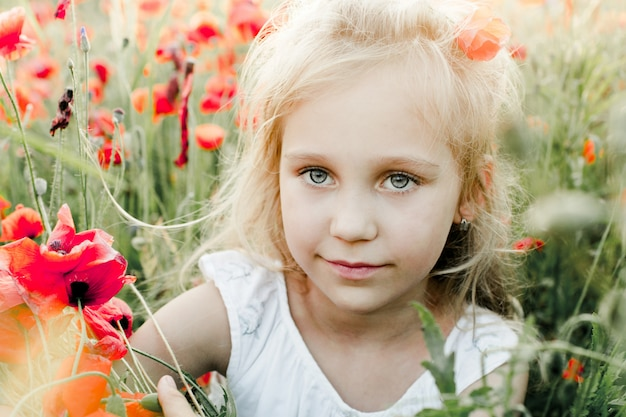 Portrait of a girl among the poppy field