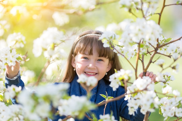 Portrait of a girl in blossoming apple tree.
