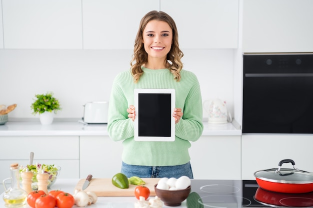 Portrait of girl cook showing tablet recipe