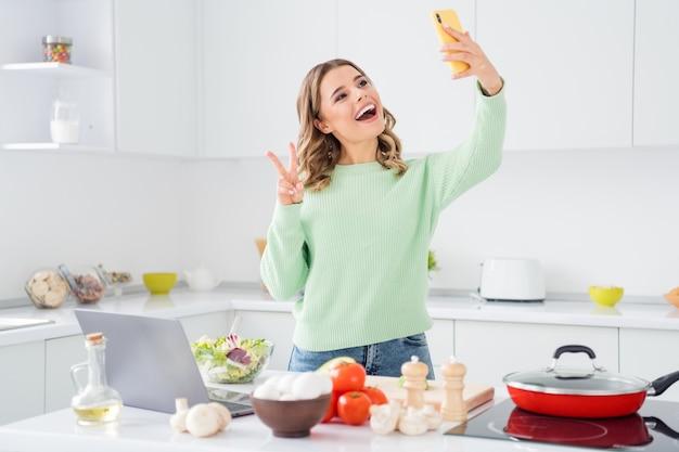 Portrait of girl cooking meal salad taking making selfie showing vsign