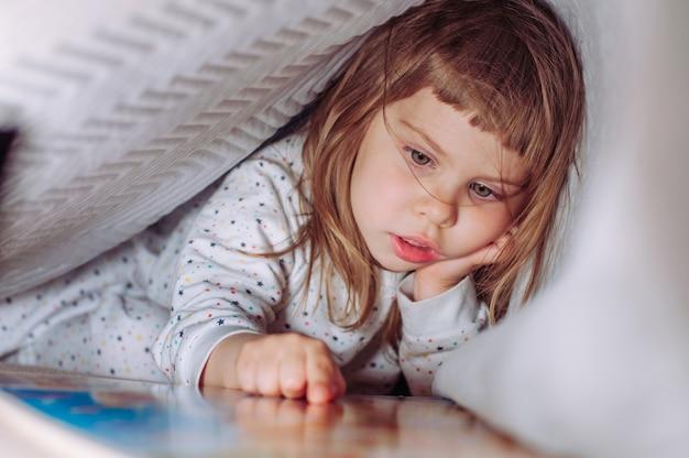 Портрет девушки накрытой одеялом чтение