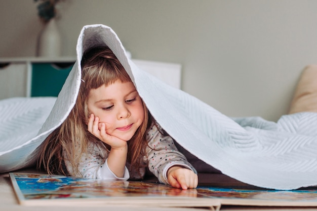 Portrait girl covered with a blanket reading