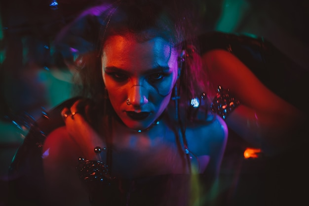 Portrait of a girl in the cyberpunk style with hair and makeup with a neon light in the garage. steampunk concept