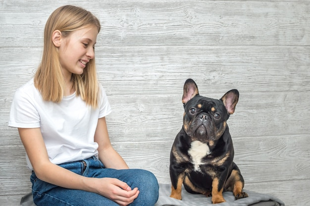 Portrait of a girl and dog french bulldog breed on gray background
