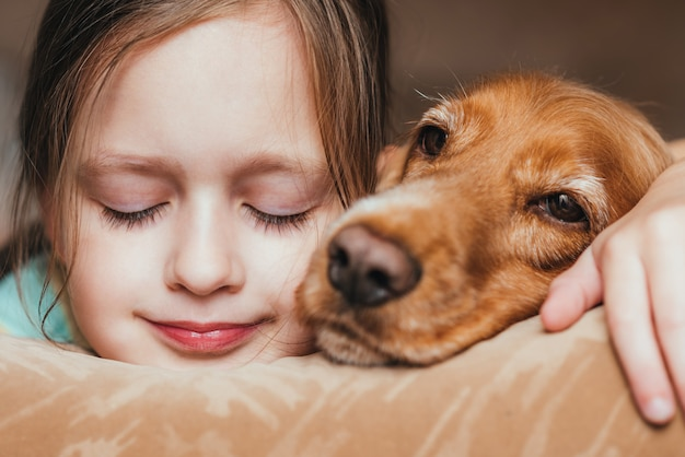 Portrait of a girl and dog lying on sofa