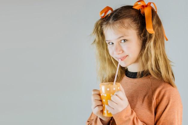 Ritratto di una ragazza che beve il succo su sfondo grigio