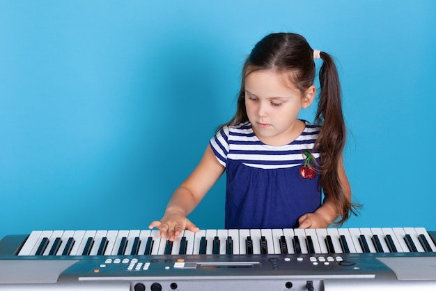 Portrait of a girl enthusiastically playing on piano