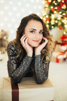 Portrait of a girl in an evening dress on the background of christmas decorations