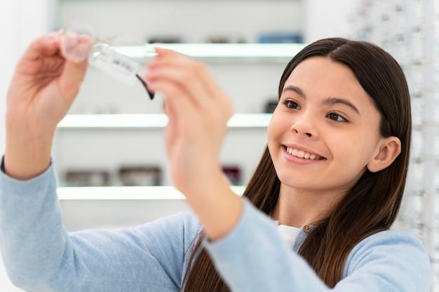 Ragazza del ritratto nel negozio di occhiali scegliendo la coppia