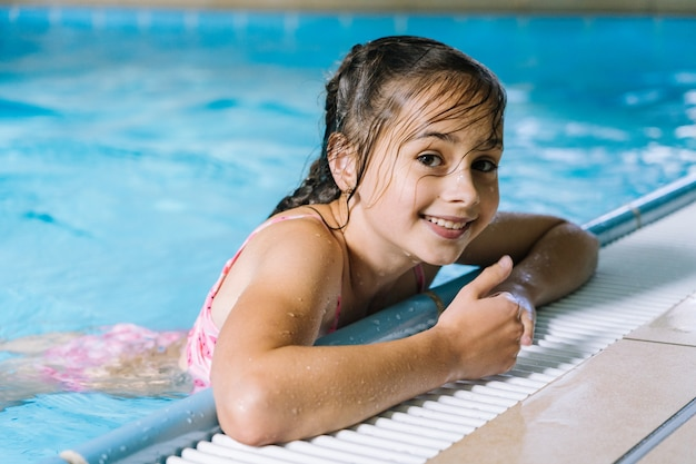 Portrait girl having fun in indoor swimming-pool. the girl is resting at the water park. active happy kid. swimming school for small children. concept friendly family sport and summer vacation