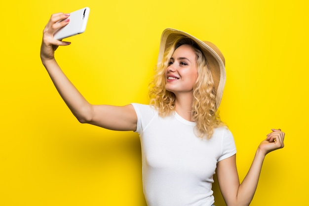 Portrait of girl having video-call with lover holding smart phone in hand shooting selfie isolated on yellow wall. enjoying weekend vacation