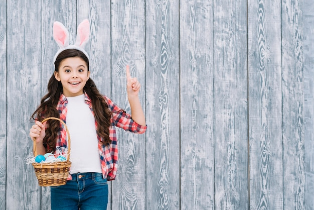 Portrait of a girl holding easter eggs basket pointing finger upward against wooden background