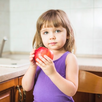 Portrait of a girl holding fresh red apple
