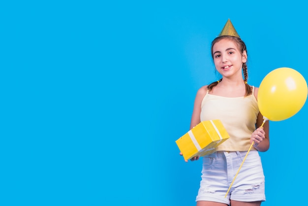 Portrait of a girl holding gift box and balloons in her hand on blue surface