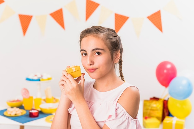 Portrait of a girl holding gift during birthday party
