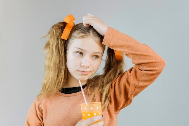 Ritratto di una ragazza che tiene un bicchiere di succo