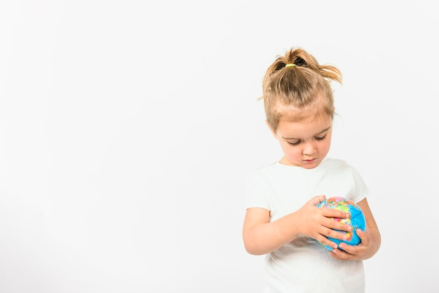 Portrait of a girl holding globe ball against white background