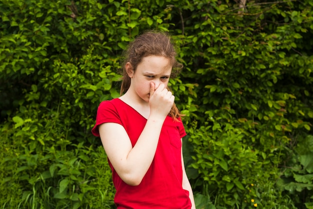 Portrait of girl holding nose in green nature looking at camera
