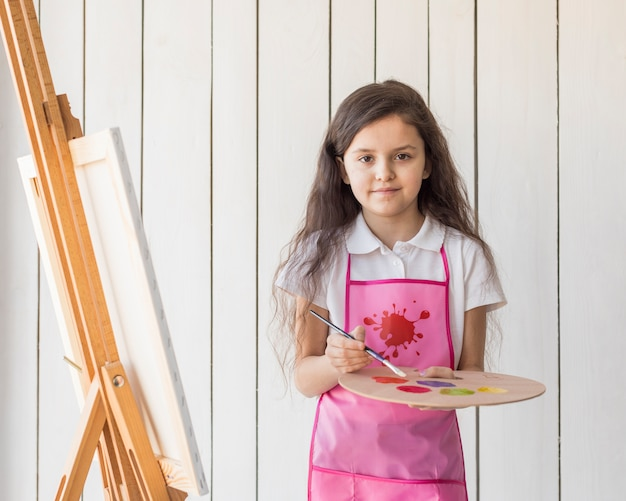 Portrait of a girl holding paint brush and palette in hand near the easel