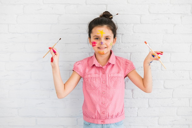 Portrait of a girl holding paint brushes in hand standing in front of white brick wall