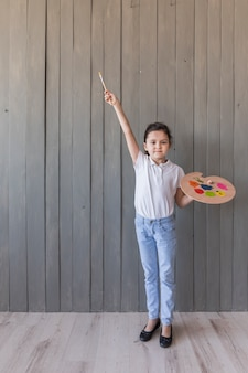Portrait of a girl holding painted palette and paint brush standing against grey wooden plank