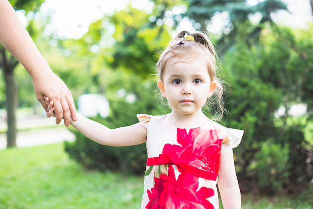 Portrait of a girl holding person hands in the garden