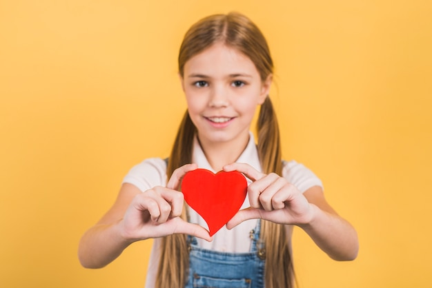 Portrait of a girl holding red heart toward camera against yellow background
