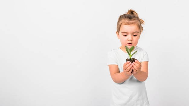 Portrait of a girl holding seedling plant in hand against white backdrop