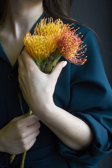 Portrait of a girl holding three yellow and orange proteas