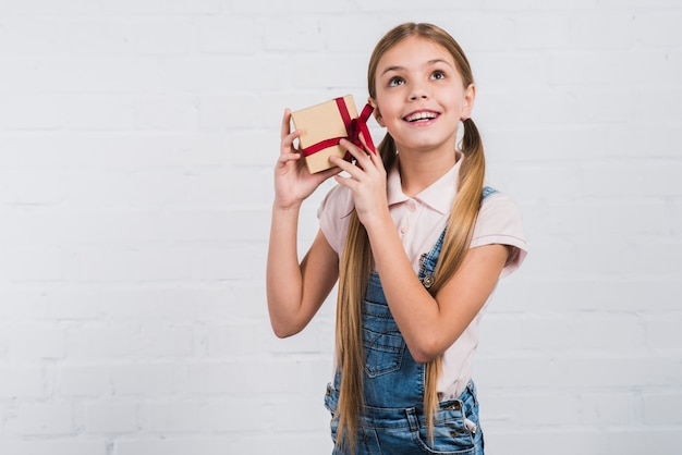 Portrait of a girl holding wrapped presents in the ear against white backdrop