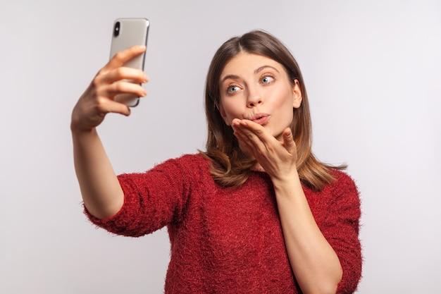 휴대 전화를 통해 화상 통화를 하고 공기 키스를 보내고 의사 소통하는 스웨터를 입은 초상화 소녀