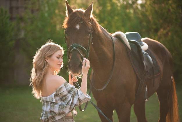 Portrait of girl inplaid shirt with black horse in the horse farm.
