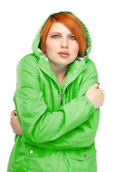 Portrait of a girl in a jacket with a trembling from the cold isolated on white