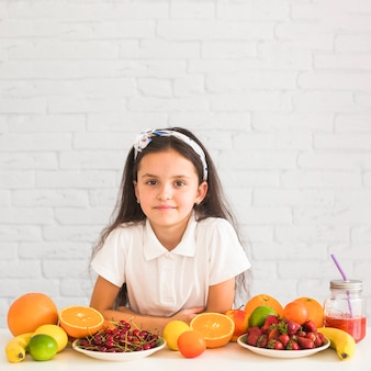 Portrait of a girl leaning on desk with many different fruits