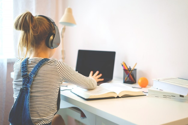Portrait of a girl learning online with headphones and laptop taking notes in a notebook sitting at her desk at home doing homework