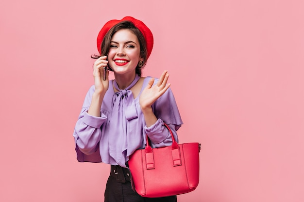 Portrait of girl in lilac blouse and red beret on pink background. woman holding small bag and talking on phone.