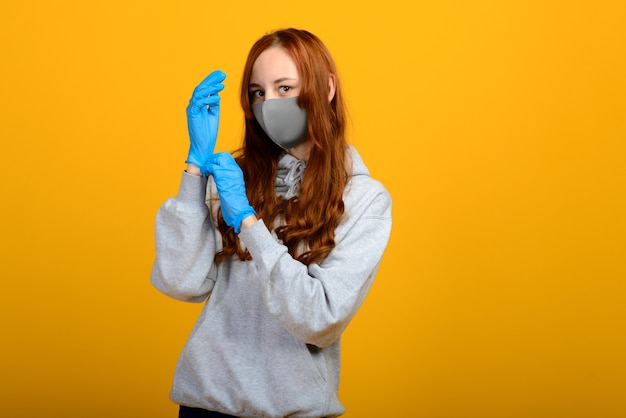 Portrait of a girl in a mask, which puts on a rubber glove. yellow background. copy space.