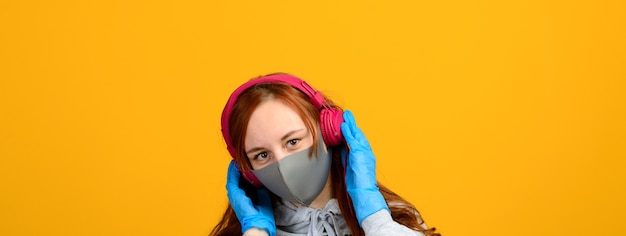 Portrait of a girl in a mask, which puts on a rubber glove. yellow background. isolation, covid-19.