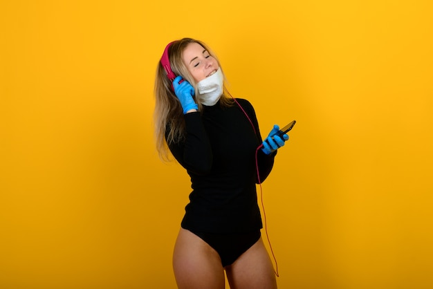 Portrait of a girl in a medical mask, which puts on a rubber glove. yellow and grey background. copy space.