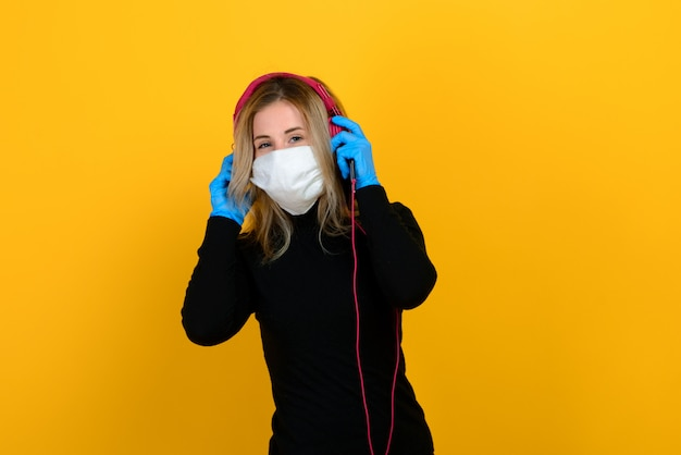 Portrait of a girl in a medical mask, which puts on a rubber glove. yellow and grey wall. copy space.