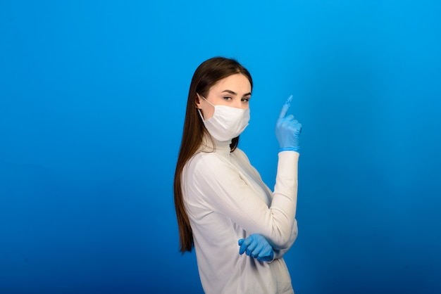 Portrait of a girl in a medical mask, which puts on a rubber glove.